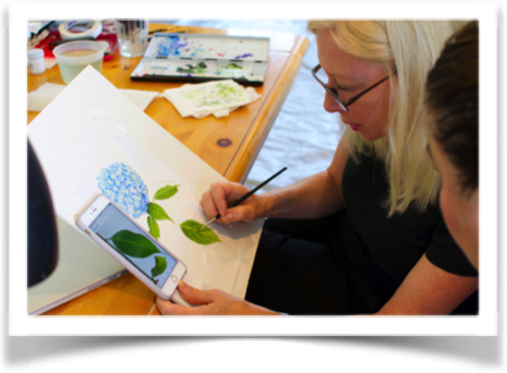 Karen Kluglein illustrates her technique to an attentive student during her 2016 East Hampton Painting Summer Flowers Workshop. Click here [https://www.facebook.com/KarenKluglein7/photos/a.128095427283780.27872.115226741903982/1066021916824455/?type=3&theater] to see the final version of this hydrangea on Karen's Facebook [https://www.facebook.com/KarenKluglein7/] page.